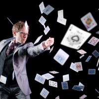 Ben Seidman Performing Magic with a deck of cards scattered